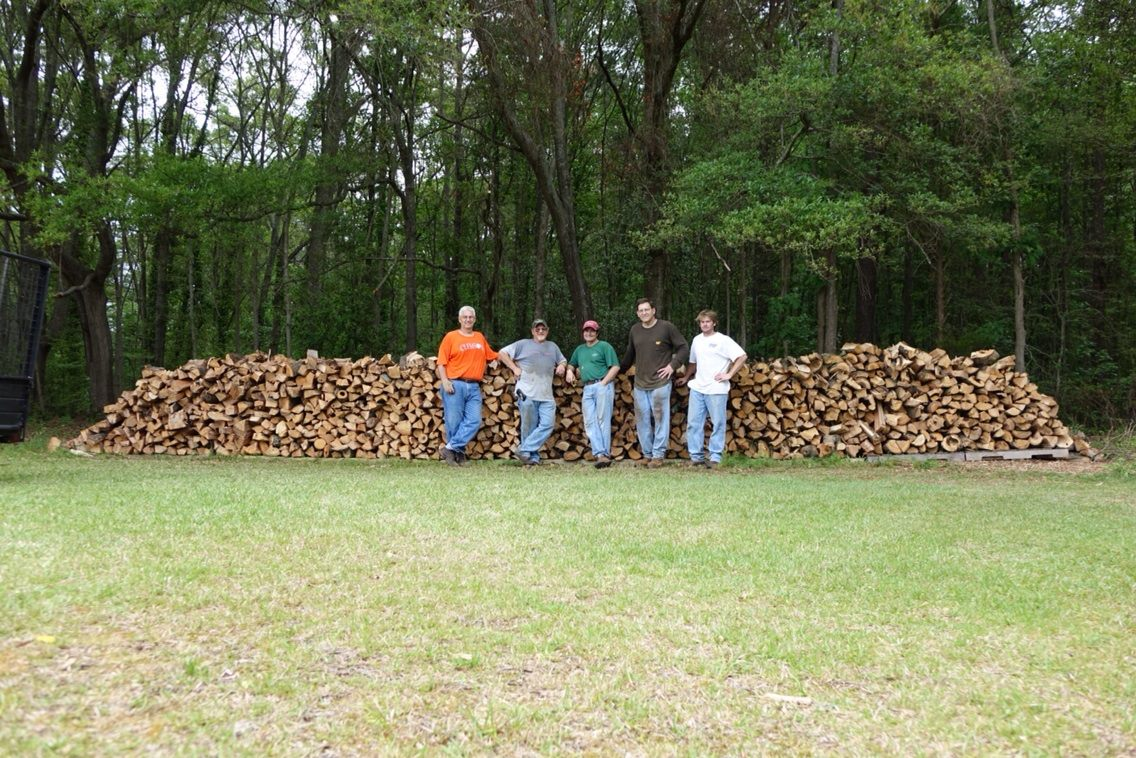 Men standing in front of woodpile